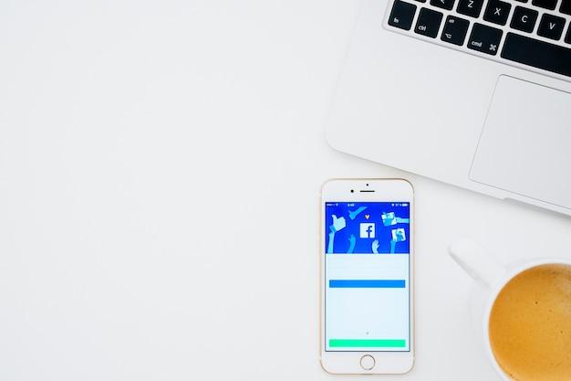 Facebook app in de telefoon met koffie en laptop