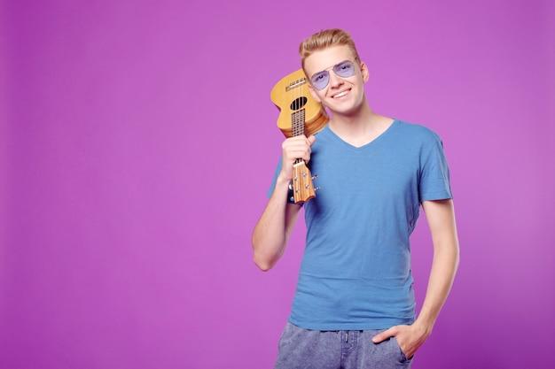 Fachion schoonheid grappige man met ukelele in handen op paarse achtergrond copyspace