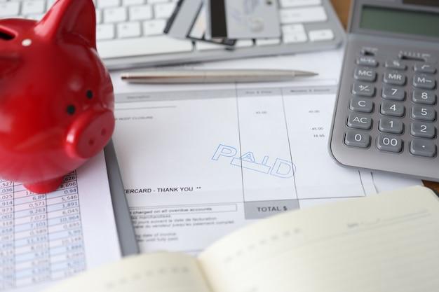 Factuur betaalde financiële rekeningbetaling en spaarvarken spaarvarken op tafelbetalingsrapport