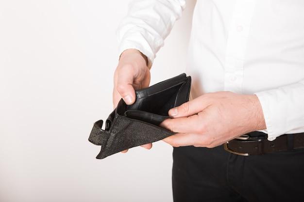 Faillissement - bedrijfspersoon die een lege portefeuille houdt. man toont de inconsistentie en het gebrek aan geld en kan de lening en de hypotheek niet betalen.