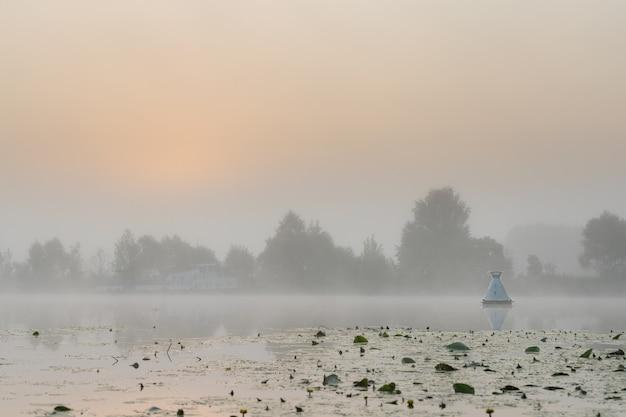 Fairway boei in dichte mist op de rivier in de vroege ochtend met de eerste zonnestralen