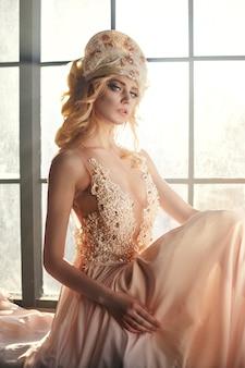 Fairy met lang blond haar in het licht is op de achtergrond van een groot raam