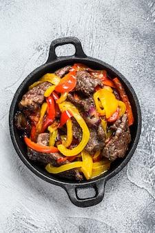 Fajitas rundvlees traditioneel mexicaans eten gerecht in een pan. bovenaanzicht.