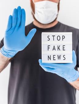 Fake news infodemics tijdens covid-19 pandemie concept. man met beschermend masker en medische handschoenen op handen met lightbox met tekst stop nepnieuws. mensen willen de waarheid weten over het coronavirus
