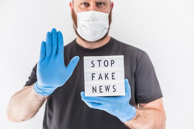Fake news infodemics tijdens covid-19 pandemie concept. man met beschermend masker en medische handschoenen op handen met lightbox met tekst stop nepnieuws.