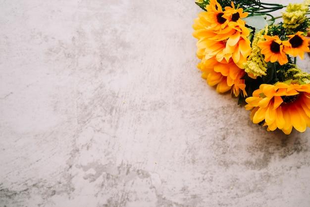Fake zonnebloemen boeket op een oude witte muur