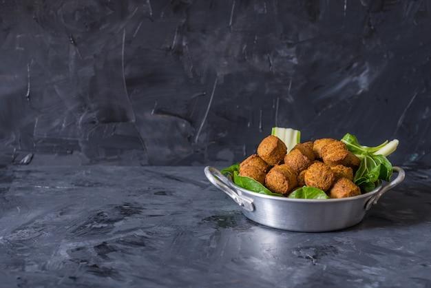 Falafel ballen geserveerd in plaat met groene bladeren op houten zwarte achtergrond