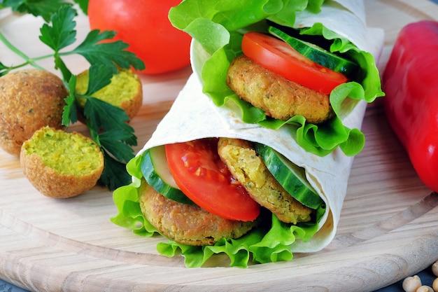 Falafel en groenten verpakt in lavash op een lichte snijplank.