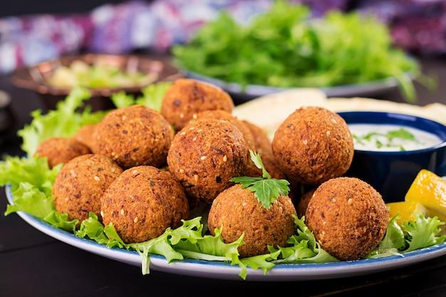 Falafel, hummus en pita. midden-oosterse of arabische gerechten op een donkere ondergrond. halal eten.