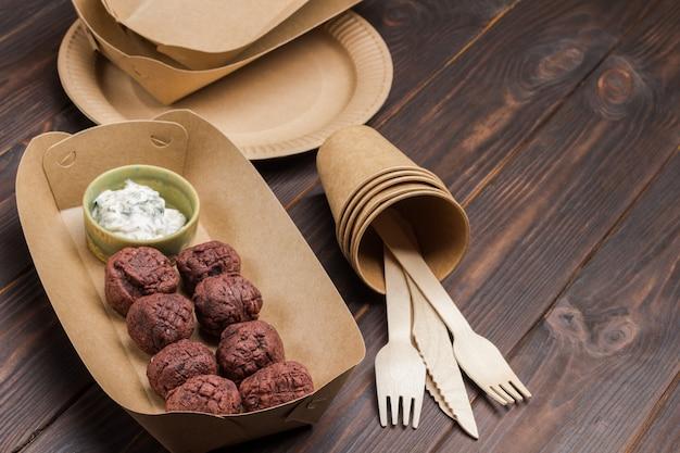 Falafel in kartonnen kom. afhaalmaaltijden in ecologische verpakking. kopieer ruimte. bovenaanzicht. donkere houten tafel.