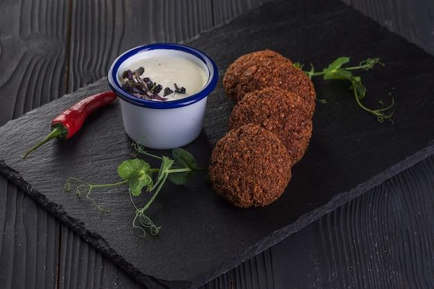 Falafel met knoflooksaus op een zwart stenen dienblad. veganistisch eten