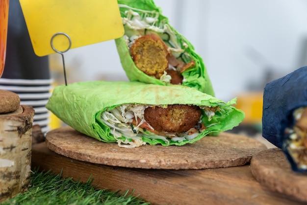 Falafel sandwich gerold in plat groen brood. vegan sandwich in lavashbrood met groenten en gefrituurde bal of pasteitjes van gemalen kikkererwten