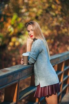 Fall concept - mooie vrouw in herfst park onder vallen gebladerte