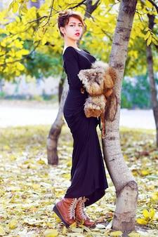 Fall fashion lifestyle portret van sexy mooie aziatische vrouw, gekleed in lange stijlvolle maxi jurk laarzen en stuk bont, poseren in stadspark in mooie zonnige herfstdag. felle kleuren.