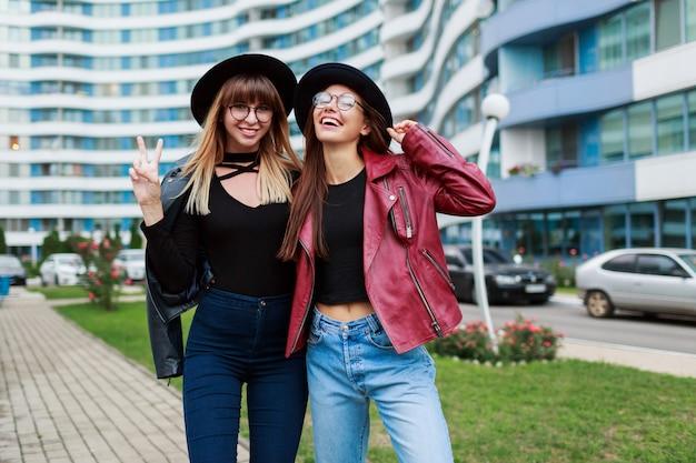 Fall fashion look. paar aantrekkelijke sierlijke meisjes in schattige ronde bril en zwarte hoeden poseren