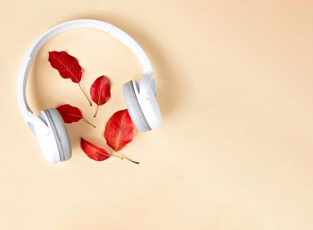 Fall flat lay compositie met rode herfstbladeren, kopje koffie en witte koptelefoon. herfst podcast achtergrond. herfst afspeellijst concept.