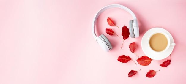 Fall flat lay compositie met rode herfstbladeren, kopje koffie en witte koptelefoon op roze achtergrond. herfst podcast achtergrond. herfst afspeellijst concept.