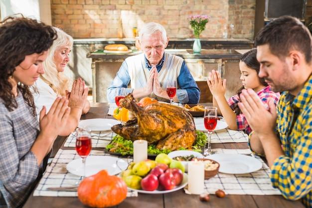 Familie aan tafel bidden voor de maaltijd
