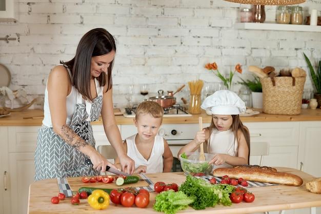 Familie bereidt lunch in de keuken. moeder leert haar dochter en zoon een salade met verse groenten te bereiden. gezonde natuurvoeding, vitamines voor kinderen