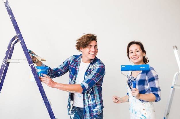 Familie bezig met herinrichting en samen muren schilderen en lachen.