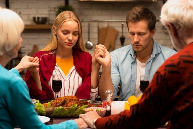 Familie bidden aan de eettafel