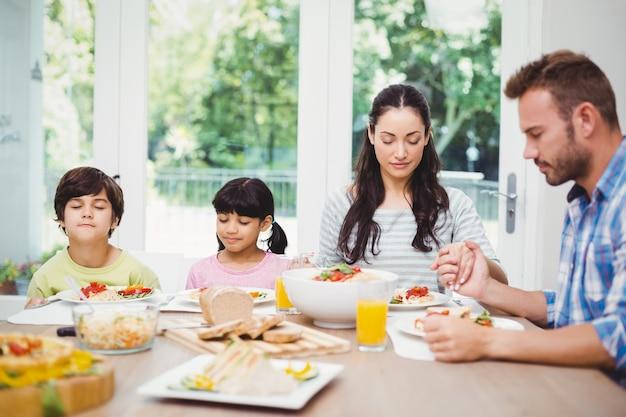 Familie bidden aan eettafel