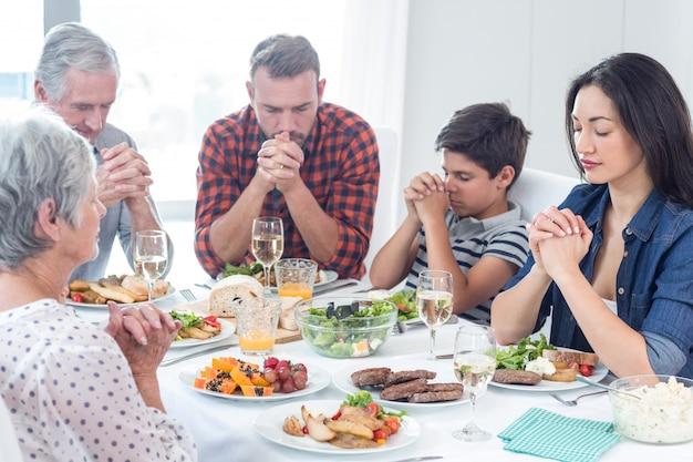 Familie bidden samen voor de maaltijd