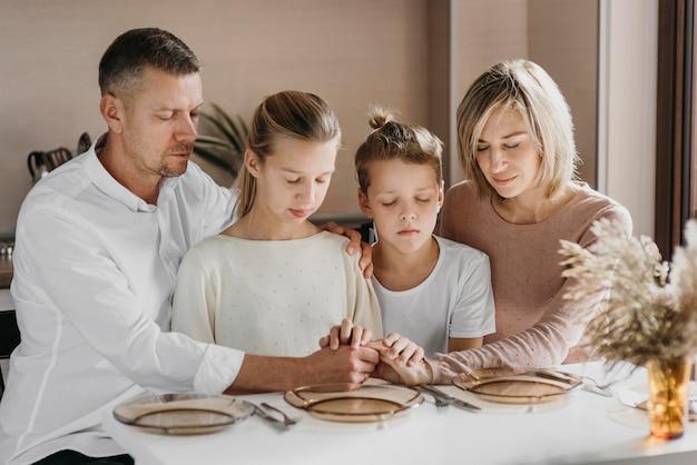 Familie bidden terwijl ze hun handen bij elkaar houden