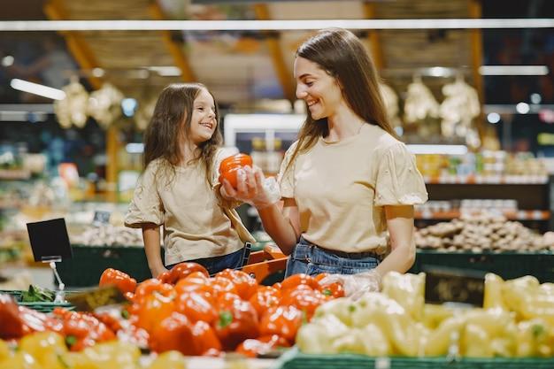 Familie bij de supermarkt. vrouw in een bruin t-shirt. mensen kiezen voor groenten. moeder met dochter.