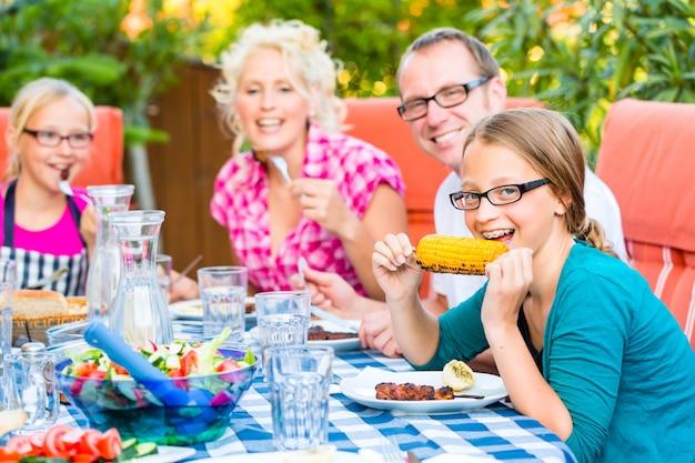 Familie bij het eten in de barbecue van de tuinzomer