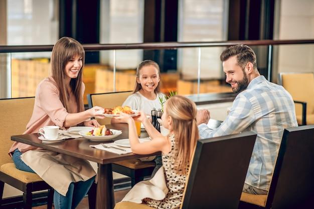 Familie bij het ontbijt. gelukkige familie aan de gediende tafel zitten en er vrolijk uitzien