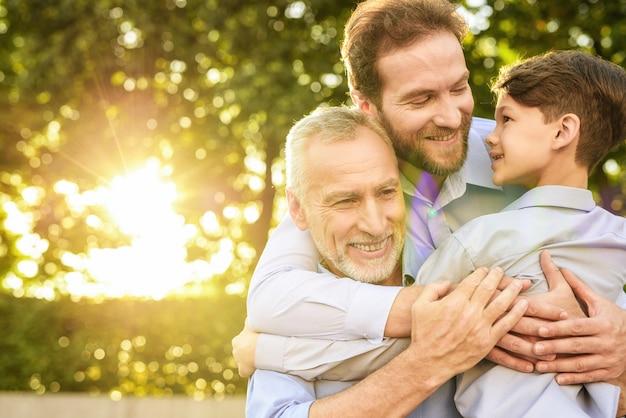 Familie bijeenkomst. zoon kleinzoon en oude man knuffels.