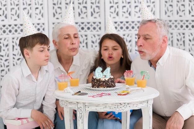 Familie blazende aantalkaarsen op verjaardagscake met glazen sap op lijst