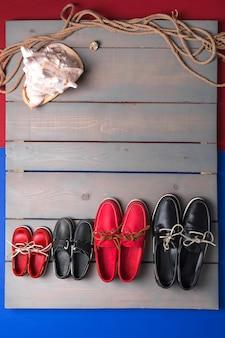 Familie bootschoenen op houten achtergrond. vier paar rode en zwarte bootschoenen op grijs bureau met kabel en schelp. familie concept