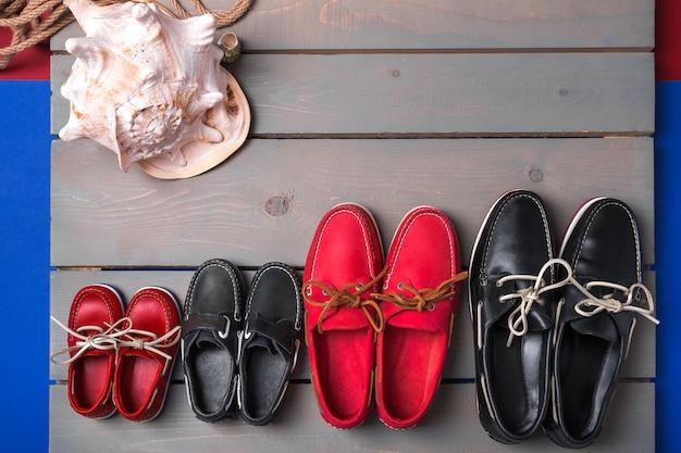 Familie bootschoenen op houten achtergrond. vier paar rode en zwarte bootschoenen op grijs bureau met kabel en schelp.