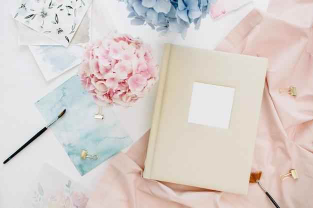 Familie bruiloft fotoalbum, pastel kleurrijke hortensia bloemboeket, peachy deken, decoratie op wit oppervlak