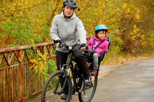 Familie buiten fietsen, gouden herfst in park