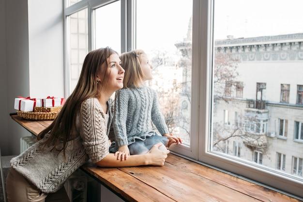 Familie concept. moeder en dochter die in venster kijken.