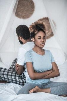 Familie, conflict. boze afrikaanse amerikaanse vrouw met gevouwen armen op borstzitting met rug naar haar echtgenoot in slaapkamer op bed