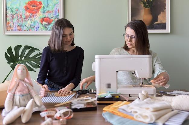 Familie creatieve handgemaakte hobby en vrije tijd, moeder en tienerdochter naaien samen konijnenspeelgoedpop. vrouw leert meisje naaivaardigheden, praten