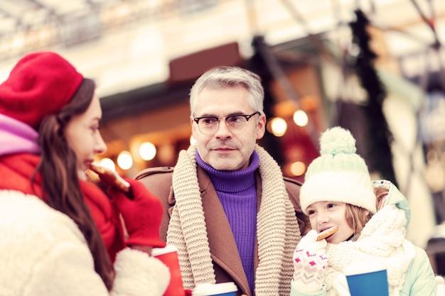 Familie dag. geconcentreerde grijsharige man met bril terwijl hij naar zijn vrouw keek