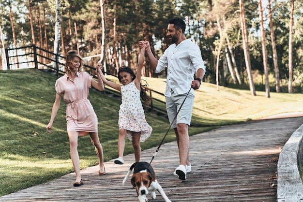Familie dag. volledige lengte van een jong gezin van drie hand in hand en glimlachend terwijl ze samen in het park wandelen