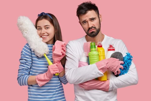 Familie deelt huishoudelijke taken samen gelukkige dame draagt spons om stof af te vegen, witte borstel, heeft tevreden uitdrukking