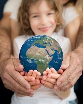 Familie die 3d planeet in handen houdt. aarde dag vakantie concept. elementen van deze afbeelding geleverd door nasa