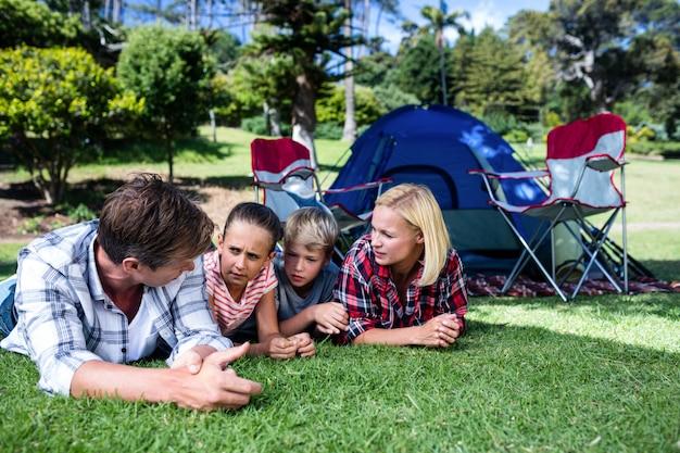 Familie die aan elkaar spreekt terwijl het liggen op gras