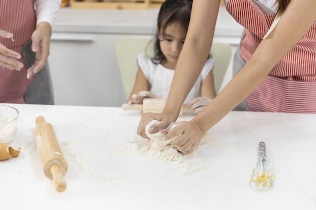 Familie die bakkerij in de keuken maakt