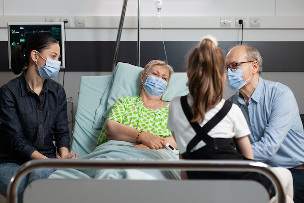 Familie die beschermend gezichtsmasker draagt tegen covid tijdens een bezoek aan zieke grootmoeder