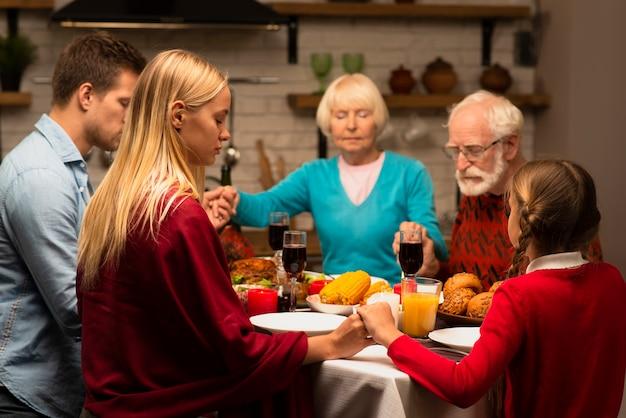 Familie die bij de dinerlijst bidt en handen houdt