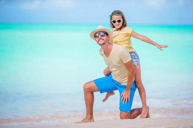 Familie die bij tropisch strand samen in caraïbisch eiland antigua en barbuda loopt