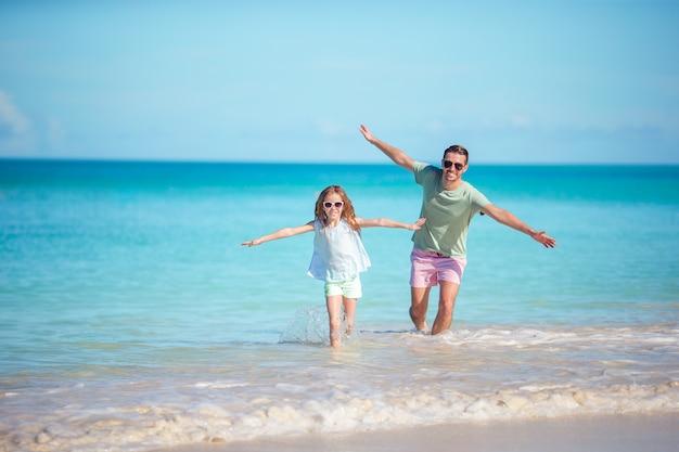 Familie die bij tropisch strand samen op tropisch carlisle baaistrand loopt met wit zand en turkoois oceaanwater bij het eiland van antigua in de caraïben.
